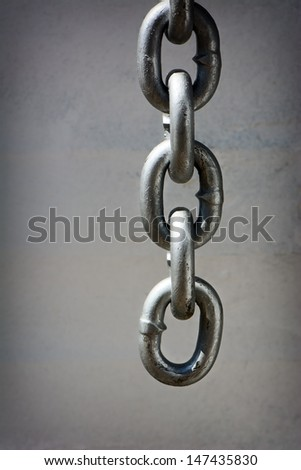 A detailed closeup macro of a heavy duty chain dangling in front of a dingy white wall.  Room for copy space. - stock photo