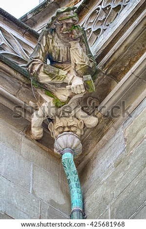 A detailed figure of a stonemason carved in stone sits over a demon on top of one of the drains on the Bern Minster Cathedral in Switzerland.
