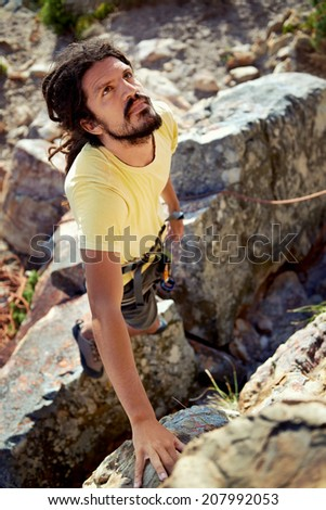 A determined man looking up at the mountain he is about to climb -Rock climbing