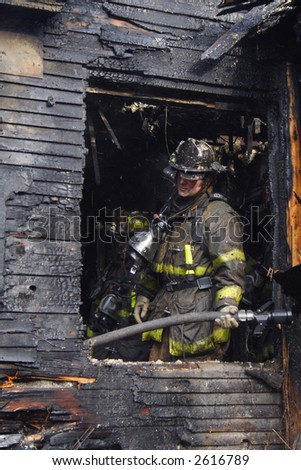 A Detroit Fireman examining the damage of an urban fire
