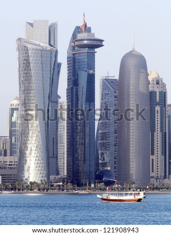 A dhow passes beneath some of the most massive buildings in Doha, Qatar, shortly before sunset in December 2012