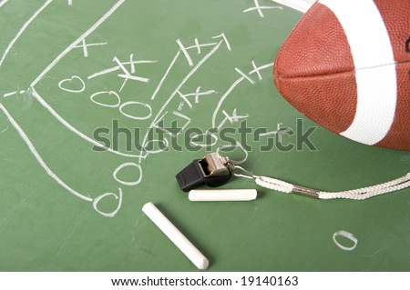A diagram of a football play on a chalkboard with a football, chalk, eraser and a whistle - stock photo