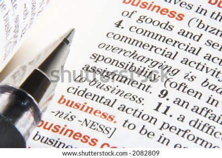 "A dictionary opened at a definition ""business"", with a pen on it - stock photo"