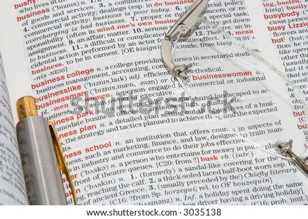 A dictionary opened at different business definitions with a pen and glasses on it