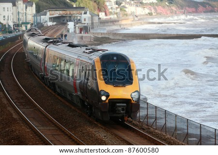A diesel train leaves dawlish Station on the famous Brunel coastal railway