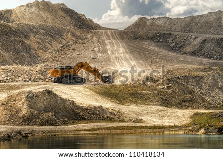 a digger in a limestone quarry - stock photo