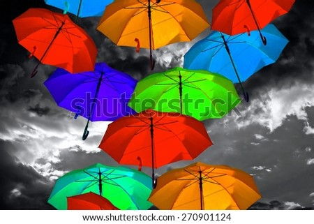 A digitally constructed painting of colorful umbrellas against a stormy sky - stock photo