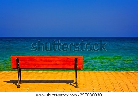 A digitally converted painting of a  lone bench overlooking the sea - stock photo