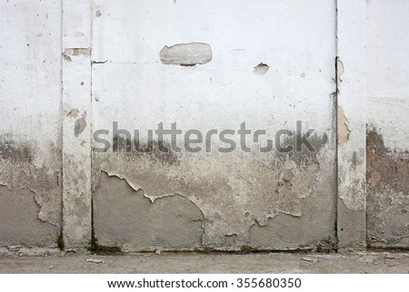 A dilapidated blank white walls with peeling paint and flooding mark for textural background.