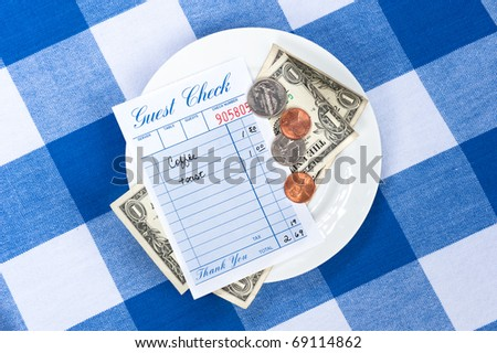 A dining check on a saucer with change from a meal payment. - stock photo