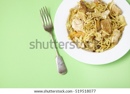 A dinner dish of chicken noodle stir fry on a pastel green background with fork and empty space at side