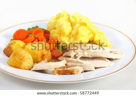 A dinner of roast chicken served with roast potatoes, mixed veg, mashed potato and gravy. - stock photo