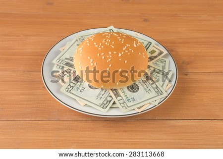 A dinner plate with burger stuffed with money on a wooden table. concept image for rich and greedy - stock photo
