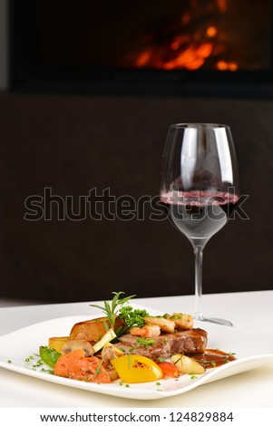 A dinner setting: Delicious juicy barbecued steak and prawns Surf and Turf with grilled tomato and roasted potatoes and a glass of good red wine - stock photo