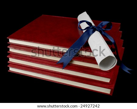 A diploma with a blue ribbon over several books. Isolated on black.