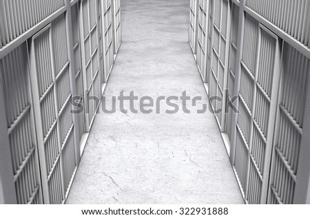 A direct top view of a row of closed jail cells between a concrete aisle lit by a single dramatic spotlight - stock photo