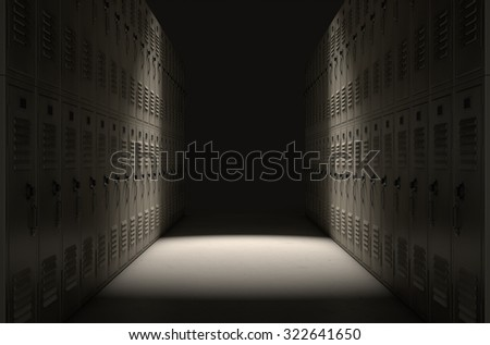 A direct top view of a row of regular school lockers in a corridor dramatically lit by a single spotlight - stock photo