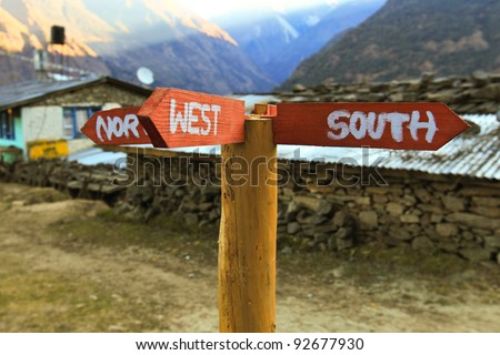 A direction pole paint with North, West, South is setting up in front of a stone house, 2 direction plates are redundant - stock photo