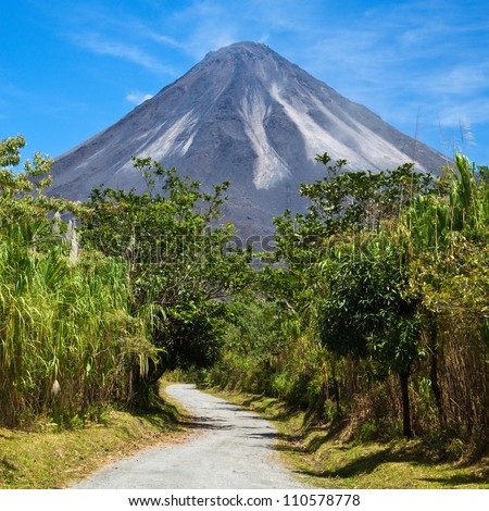 A dirt road leading to the active side of Arenal Volcano, Costa Rica. - stock photo
