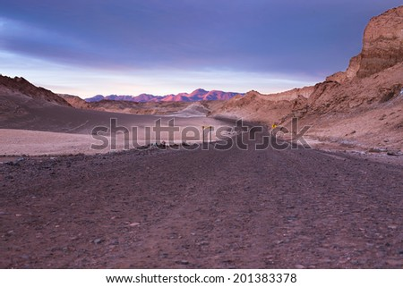A dirt road leads to the distant beautiful mountains of the atacama desert  - stock photo
