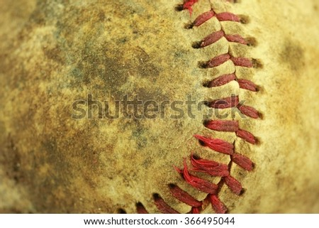 A dirty baseball with red stitches.