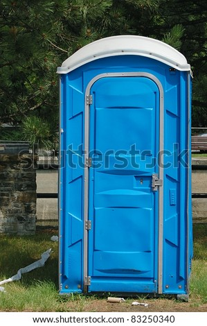A Dirty, Blue Portable Toilet in a Park, with Scraps of Toilet paper Littering the Grass