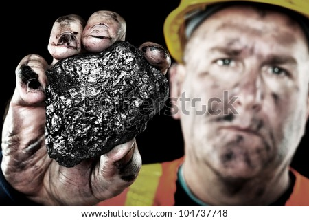 A dirty coalminer displays a lump of coal as a power and energy source. - stock photo