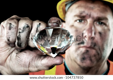 A dirty diamond miner covered in soot shows off a precious gem found in a coal mine. - stock photo