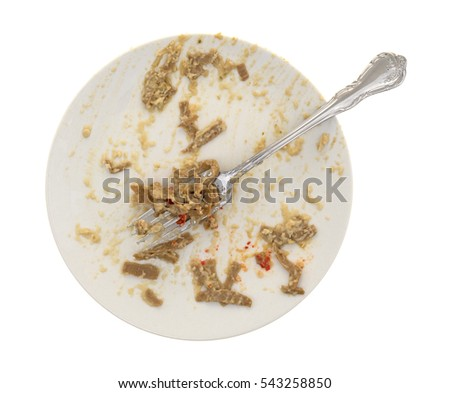 A dirty dish with leftover edamame fettuccine plus a fork isolated on a white background.