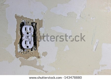 A dirty electrical outlet exposed during a renovation and the surrounding dry wall.   - stock photo