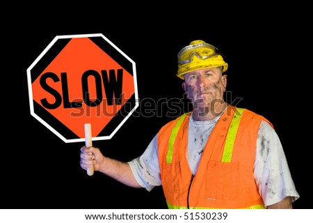 A dirty, greasy utility construction worker with a yellow hard hat, safety goggles, and a reflective orange vest holding up a warning slow sign. - stock photo