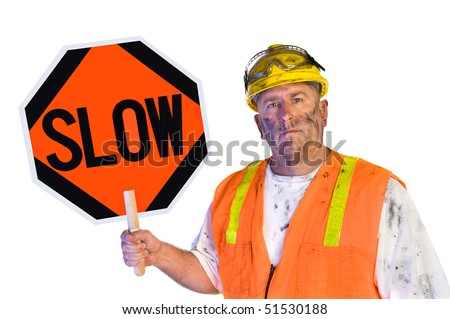 A dirty, grungy, greasy utility construction worker with hard hat, orange vest and eye protection holds up a slow sign.  Isolated on white and can be used as a design element.