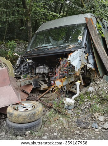 A discarded van in woodland that has been pillaged for parts and scrap