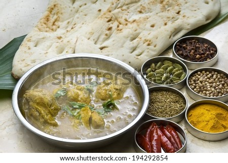 A dish of food and six ramekins of spices. - stock photo