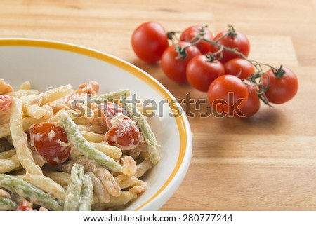 a dish of multi colored trofie with salmon and cream - stock photo