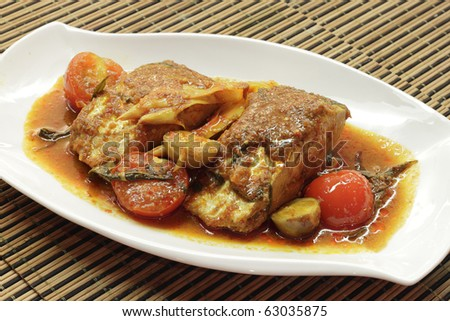 A dish of spicy and sour wolf-herring fish served with herbs, tomato, lemon and carrots.