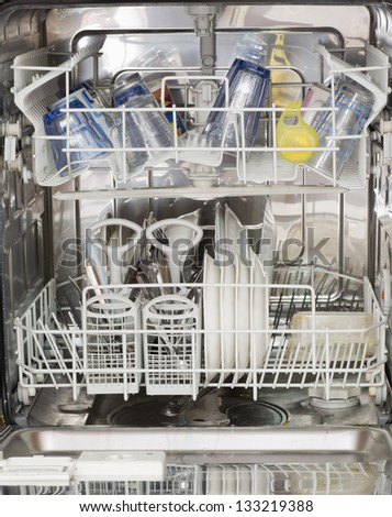 a dishwasher full of glasses, plates and cutlery to be washed - stock photo