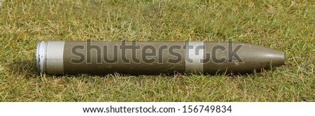 A Display Military Artillery Shell Laying on the Grass. - stock photo