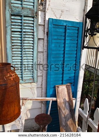 A display of old shutters with peeling paint on an aging porch full of vintage items.  - stock photo