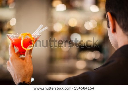 a distinguished young man holding a cocktail and celebrating - stock photo