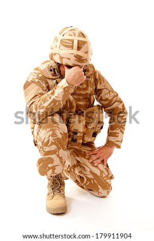 A distraught soldier on one knee with one hand covering his face, possibly suffering from shell shock or Post Traumatic Stress Disorder - stock photo