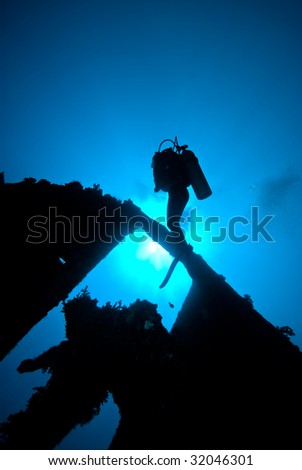 A Diver at the stern of a shipwreck - stock photo
