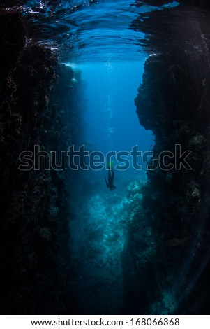 A diver descends in a large crevice eroded into an island in the Solomon Islands. This area is known for its extremely high marine biodiversity, traditional culture, and excellent scuba diving. - stock photo