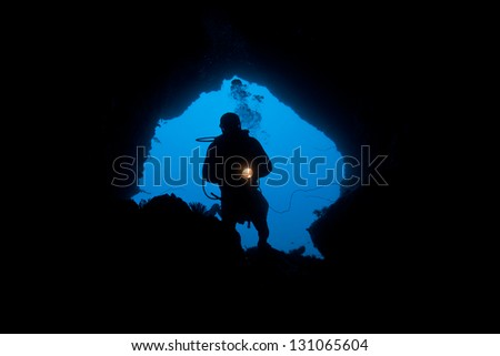 A diver explores a dark cave in North Sulawesi, Indonesia.  Caves offer another type of habitat for reef organisms to utilize. - stock photo