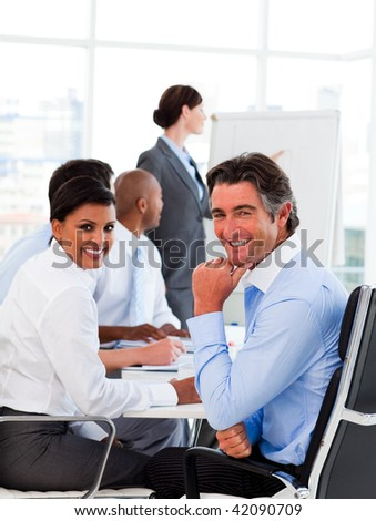 A diverse business group at a meeting smiling at the camera