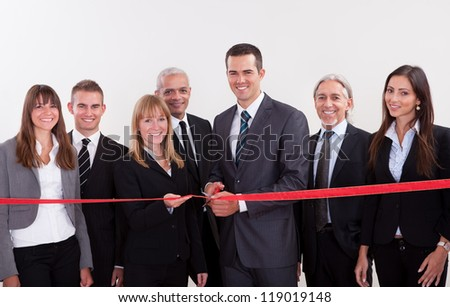 A diverse group of management level business employees about to cut the red ribbon and launch a new business venture