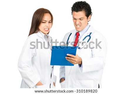 A diverse male, female, hispanic, Asian team of doctors reviewing medical charts together grimacing with shocked, pained reaction, horrified at bad diagnosis. Horizontal - stock photo
