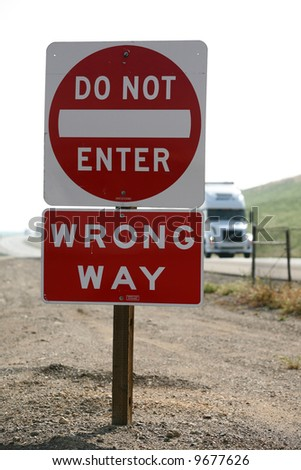 "a ""do not enter"" ""wrong way"" sign on a freeway with a ""semi truck"" behind it - stock photo"