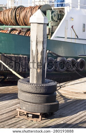 A dock pylon with used tires around it are used as means to tie up barges as they rest in their slips  - stock photo