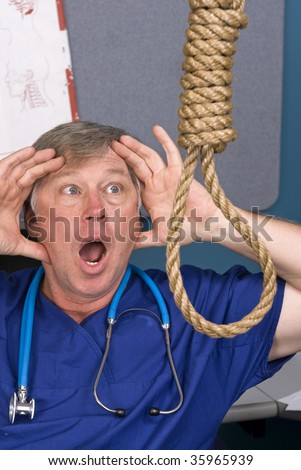 A doctor acts in shock as he discovers a noose hanging in his office. - stock photo